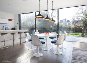 Orangery with white tulip table, wooden floor, bar and tulip chairs in blue