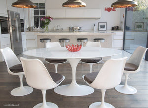 Close up of white tulip table and chairs with grey cushions in front of kitchen bar