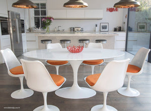 Close up of white tulip table and chairs with orange cushions in front of kitchen bar