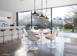 Orangery with white tulip table, wooden floor, bar and tulip chairs in orange