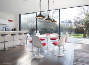 Orangery with white tulip table, wooden floor, bar and tulip chairs in red