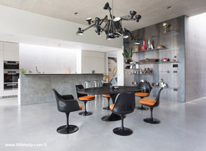 The largest Saarinen Black Tulip Table with Orange cushions dominates the room