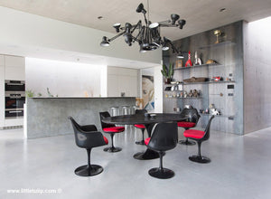 The largest Saarinen Black Tulip Table with Red cushions dominates the room
