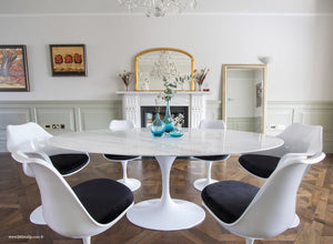 Close up of Carrara marble table next to a fireplace with matching tulip chairs in black
