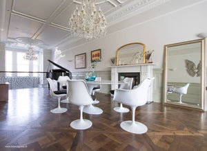 Large dining room with chandelier, piano, fireplace, Saarinen table and Tuilip Chairs
