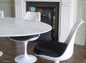 Tulip side chair with black cushion against matching marble table and fireplace