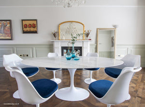Close up of Carrara marble table next to a fireplace with matching tulip chairs in blue
