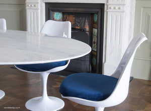 Tulip side chair with blue cushion against matching marble table and fireplace