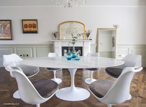 Close up of Carrara marble table next to a fireplace with matching tulip chairs in grey