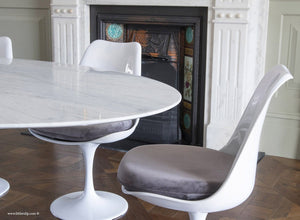 Tulip side chair with grey cushion against matching marble table and fireplace