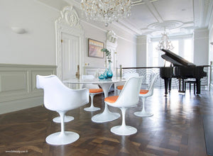 Classic dining room with piano, wooden floor, marble tulip table and 6 chairs with orange cushions