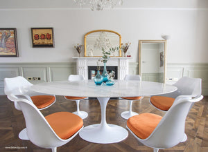 Close up of Carrara marble table next to a fireplace with matching tulip chairs in orange