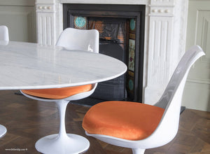 Tulip side chair with orange cushion against matching marble table and fireplace