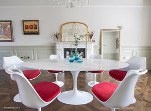 Close up of Carrara marble table next to a fireplace with matching tulip chairs in red