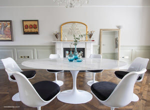 Oval marble Tulip Table with 6 Tulip Side chairs in black on wooden floor