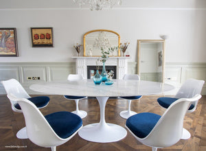 Oval marble Tulip Table with 6 Tulip Side chairs in blue on wooden floor