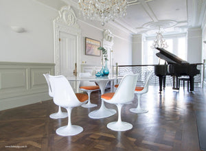 Beautiful dining room with grand piano & Tulip dining set with orange cushions