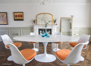 Oval marble Tulip Table with 6 Tulip Side chairs in orange on wooden floor