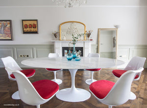 Oval marble Tulip Table with 6 Tulip Side chairs in red on wooden floor