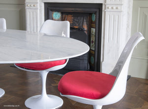 Tulip Side Chair with red cushion sitting next to the edge of a Marble Tulip table