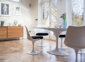 Wooden orangery floor, tulip chair with a black seat cushion
