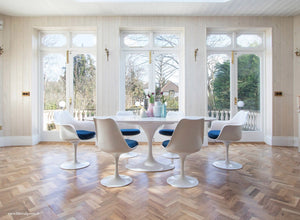 Room view with white oval Tulip Table and Chairs in blue