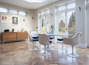 Naturally lit room with wood flor, large tulip table and chairs with blue cushions