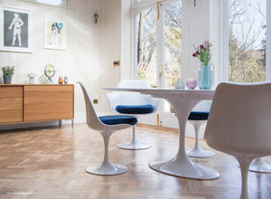 Wooden orangery floor, tulip chair with a blue seat cushion