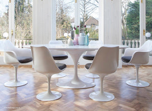 Main view of large oval white tulip table and black cushioned side chairs