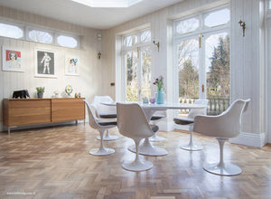 Naturally lit room with wood flor, large tulip table and chairs with grey cushions