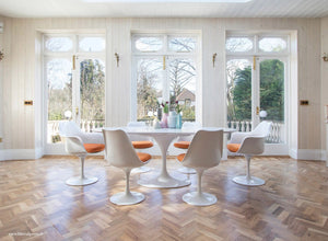Room view with white oval Tulip Table and Chairs in orange