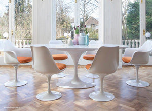 Main view of large oval white tulip table and orange cushioned side chairs
