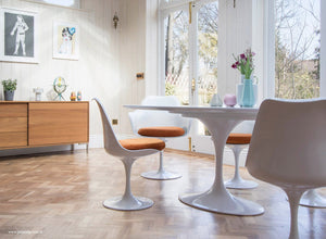 Wooden orangery floor, tulip chair with a orange seat cushion