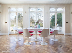 Room view with white oval Tulip Table and Chairs in Red