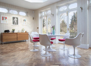 Naturally lit room with wood flor, large tulip table and chairs with red cushions