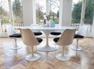 Side view of white tulip 200cm table and tulip side chairs with black cushions