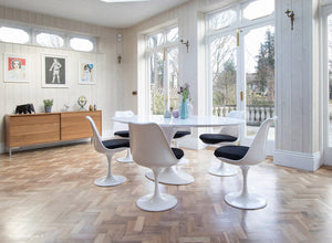 Large white oval tulip table and six chairs with black cushions and wooden floor