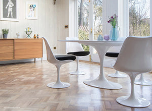 white tulip side chairs with black cushions and wooden flooring