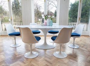 Side view of white tulip 200cm table and tulip side chairs with blue cushions