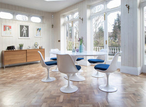 Large white oval tulip table and six chairs with blue cushions and wooden floor