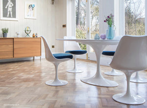 white tulip side chairs with blue cushions and wooden flooring