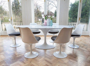 Side view of white tulip 200cm table and tulip side chairs with grey cushions