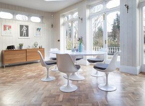 Large white oval tulip table and six chairs with grey cushions and wooden floor