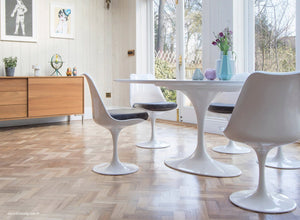 white tulip side chairs with grey cushions and wooden flooring