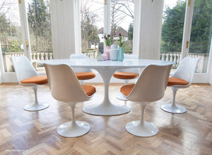 Side view of white tulip 200cm table and tulip side chairs with orange cushions