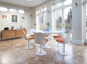 Large white oval tulip table and six chairs with orange cushions and wooden floor