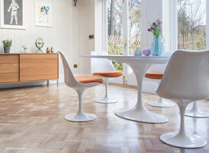 white tulip side chairs with orange cushions and wooden flooring