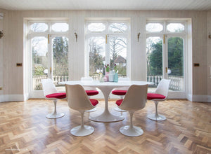 An oval large dining table in white with matching tulip side chairs