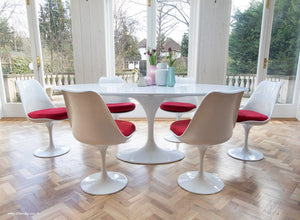 Side view of white tulip 200cm table and tulip side chairs with red cushions