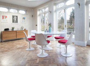 Large white oval tulip table and six chairs with red cushions and wooden floor